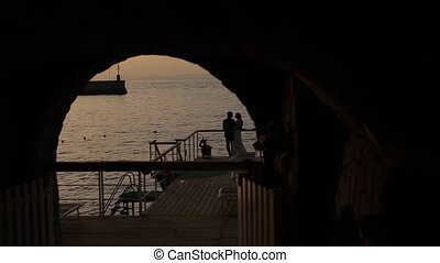 In the arch, silhouettes of the bride and groom against the background of the sea