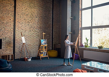 Nice pretty woman standing in front of the easel