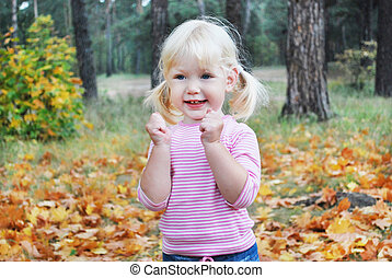 In the autumn forest little blonde girl enthusiastically shouts