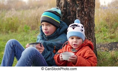 in the autumn Park children sitting on the lawn and drink hot tea, walk in the fresh air