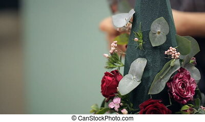 In the background female hands filling florist bouquet decorations