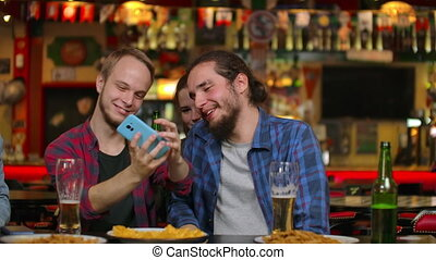 In the Bar or Restaurant Hispanic man Takes Selfie of ...
