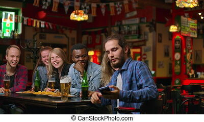 In the Bar or Restaurant Hispanic man Takes Selfie of Herself and Her Best Friends. Group Beautiful Young People in Stylish Establishment