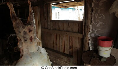In the barn hanging crucified ram, without a skin, an animal carcass, separate