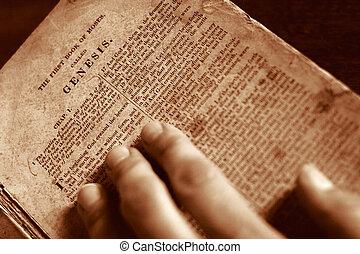 In the Beginning - A hand on the bible with page turned to ...