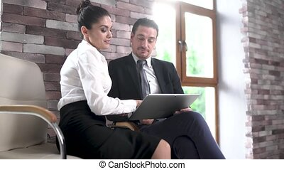 In The Business Center in the Office For Negotiations a Man and a Woman are Reviewing Documents on a Tablet.