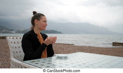 In the cafe on the banks of a woman drinking warm beverage.
