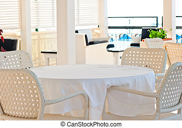 in the cafeteria wicker chairs and tables covered with cloth