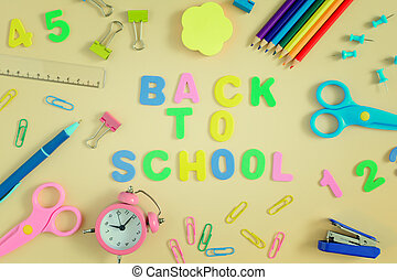 In the center of table the inscription is BACK TO SCHOOL, made in colored letters. Bright colored school and office supplies are arranged around.