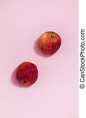 In the center on a pink background are two red apples