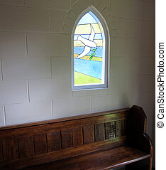 In the Chapel - A stained-glass window above a church pew in...