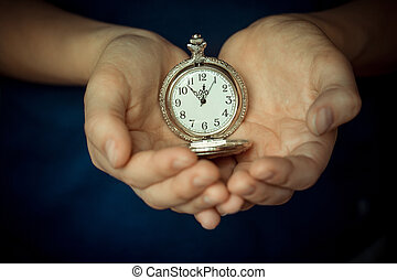 In the children's palms the old clock. Conceptual photography. The time is 11.55. Five minutes to twelve.