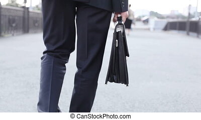 In the city - Businessman with a briefcase walking with...