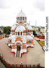 In the city, next to residential buildings, behind the fence in the churchyard, there is a red brick Orthodox church with white trim, round silver domes and golden crosses.