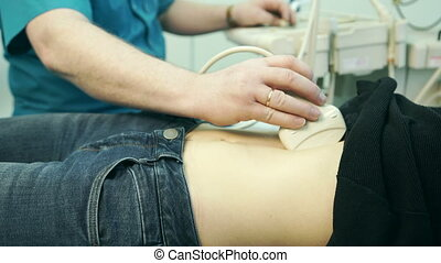 In the clinic doctor performs an abdominal ultrasound young blonde.