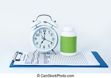 White alarm clock and pills bottle on the table with patient file