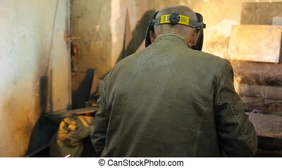 In the closed workshop welder does the job in a protective mask.