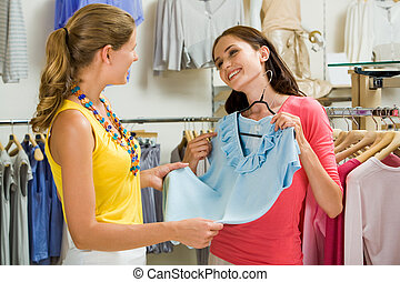 In the clothing department - Image of pretty girl showing ...