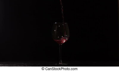 In the darkness empty transparent glass filled with red wine.