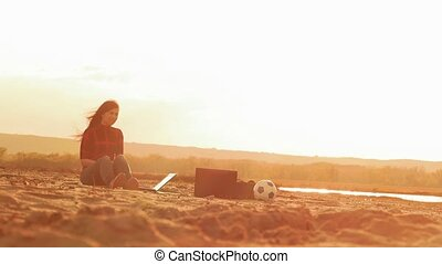 in the evening girl on the beach with a laptop slow motion video