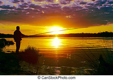 A single man on the quiet river in the rays of a evening sun