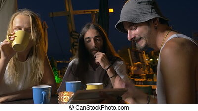 In the evening on the street, friends drink tea and watch videos on the tablet. A man shows on the screen and says something, the other man laughs
