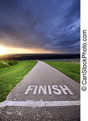 Asphalt road with inscription FINISH and sunrise in background