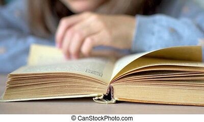 In the foreground is a book. A girl is reading a book. Close up view.