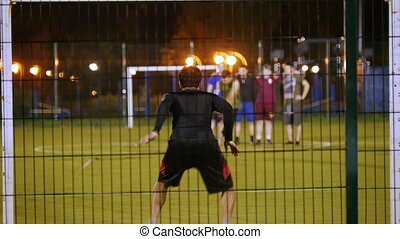 In the foreground, the goalkeeper, the other player kicks...