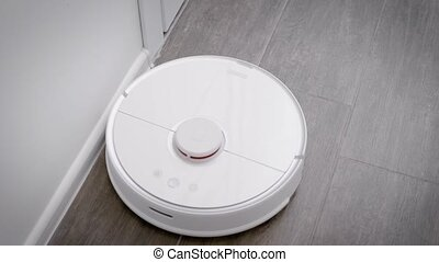 in the frame is a robot vacuum cleaner that cleans the floor...