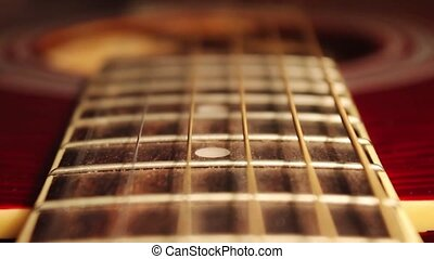 In the frame of the neck of an acoustic guitar, strings and...