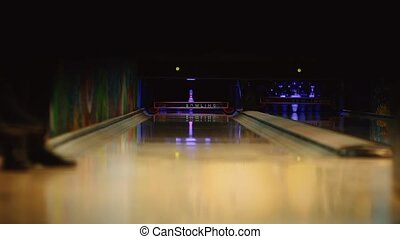 In the game club for bowling, the player throws a bowling ball that knocks down skittles. Close-up, legs running along the path and throwing a ball into the pins.