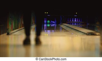 In the game club for bowling, the player throws a bowling ball that knocks down skittles. Smooth movement of the focus, from the front to the back. The player knocked out the strike and legs dance the dance of the dance.