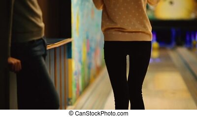 In the game club for bowling, the player throws a bowling ball that knocks down skittles. The girl throws a ball on the pins and dances a victorious dance.