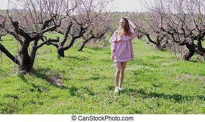 in the garden of flowering trees goes blonde girl in pink...