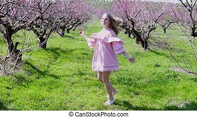 in the garden of flowering trees goes blonde girl in pink dress