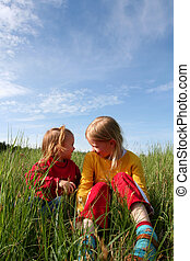 In the grass - Children sitting in the grass on a blue sky...