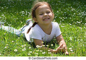in the grass - little girl on the meadow. summer time.