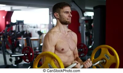 In the gym, a man makes swings with muscular arms