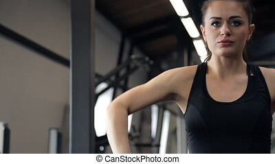 In the gym beautiful woman raises the bar with a curved neck.