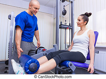 In the gym - Young woman working in the gym with personal...