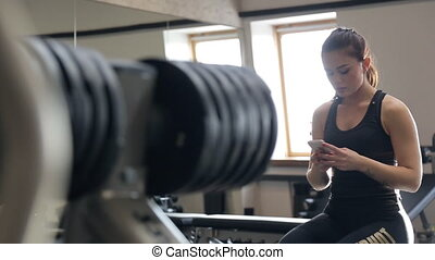 In the gym, the background a woman writing sms on a white phone