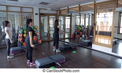 In the gym three women doing workout in front of step aerobics.