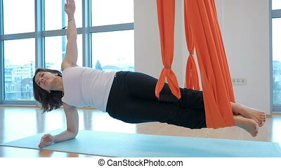 In the gym woman holding horizontal legs in a hammock. Pass...