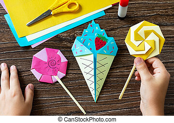 In the hands of a child origami paper ice cream and lollipop on a wooden table. Children's art project, handmade, crafts for children.