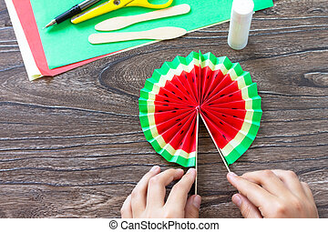 In the hands of a child Paper Fan watermelon on a wooden table. Childrens art project, handmade, crafts for children.
