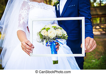 in the hands of the newlyweds frame with a wedding bouquet