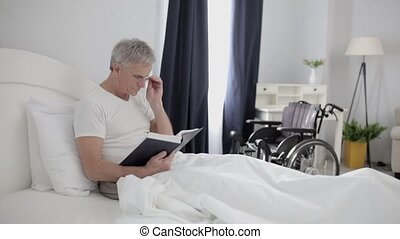 In the Hospital An Adult Man with Gray Hair is Lying on a Bed in His VIP Room.