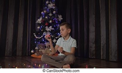 In the living room the child is sitting on the floor next to a decorative Christmas tree and curiously shakes the snow globe in which decorative snow and santa