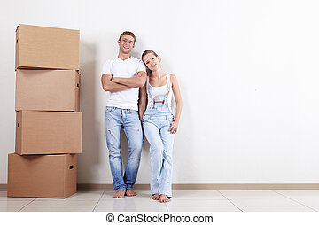 In the new apartment - Young happy couple with boxes in...